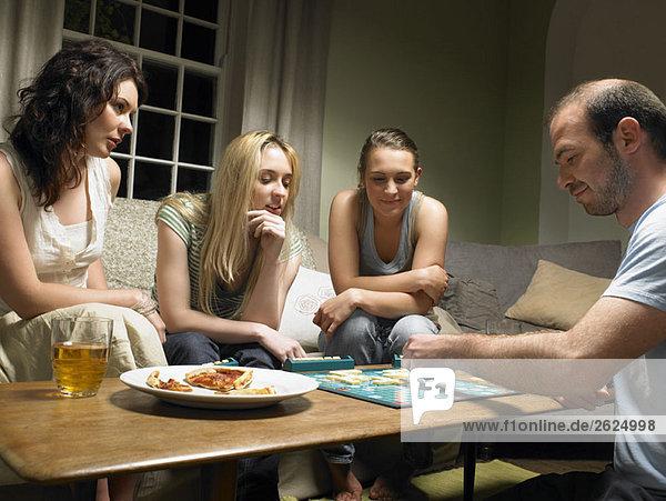 Vier junge Leute spielen Scrabble
