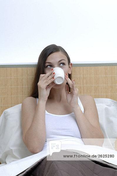 Frau in ihrem Bett mit einem Becher