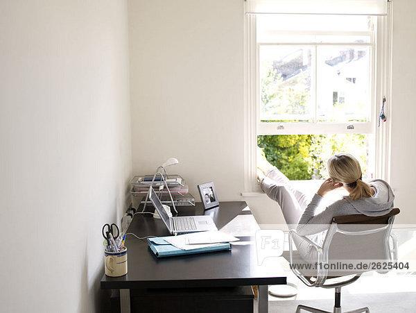 Frau sitzt im sonnigen Home-Office