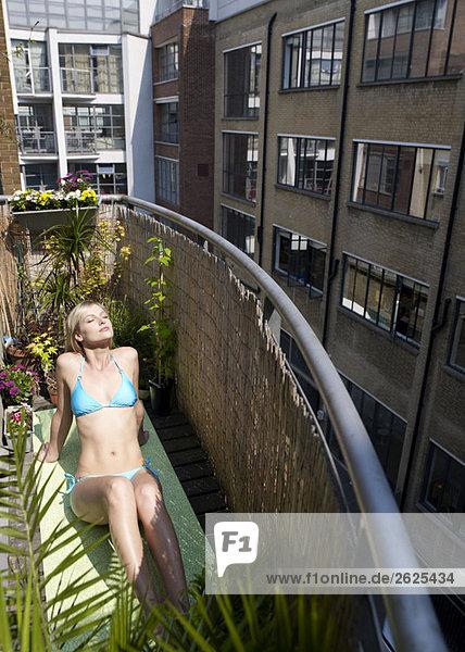 Frau beim Sonnenbaden auf dem Stadtbalkon