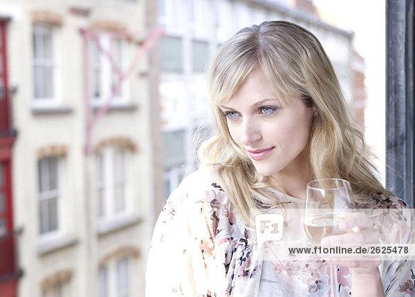 Frau gegen Fenster mit Weinglas