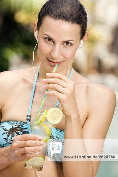 Junge Frau im Bikini mit Zitronengetränk