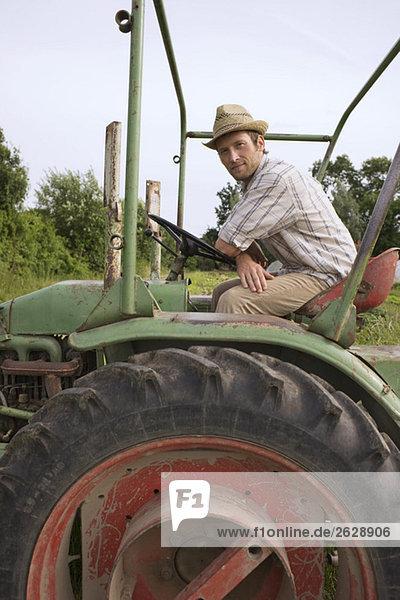 Portrait eines Bauern auf einem Traktor