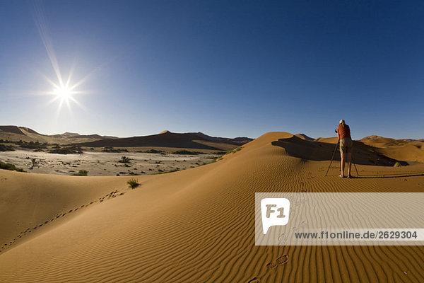 Afrika  Namibia  Fotograf in der Namib Wüste  Rückansicht