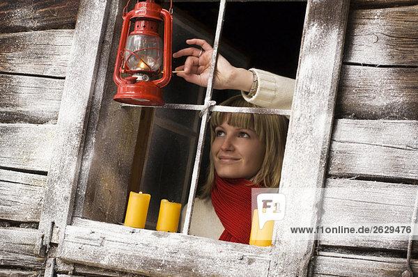 Austria  Salzburger Land  Young woman lighting storm lamp
