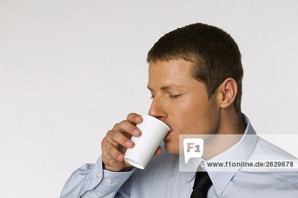 Businessman drinking cup of coffee  portrait