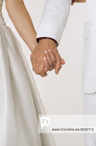 Braut und Bräutigam beim Händchenhalten  Mittelteil  Nahaufnahme