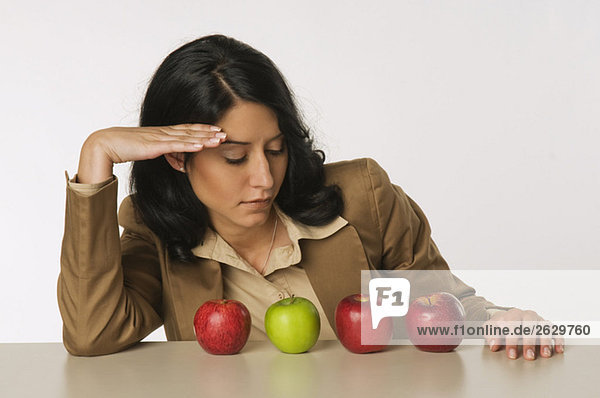 Junge Frau beim Betrachten von Äpfeln  grüblerisch  Porträt