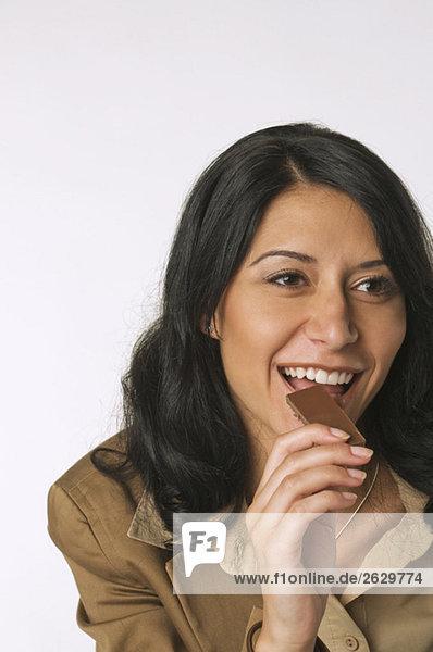 Junge Frau isst Schokoriegel  lächelnd  Portrait