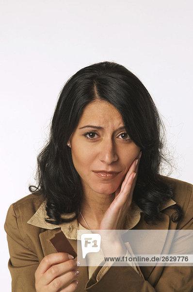 Junge Frau hält Schokoriegel  Portrait