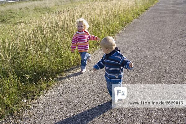 Kleines Mädchen (2-3) und Junge (1-2) laufen über den Weg