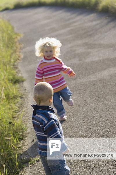 Kleines Mädchen (2-3) und Junge (1-2) beim Spielen auf dem Pfad
