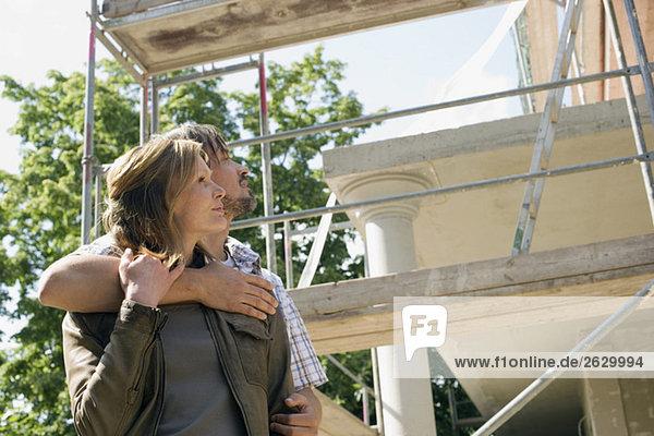 Junges Paar umarmt sich vor dem Haus im Bau