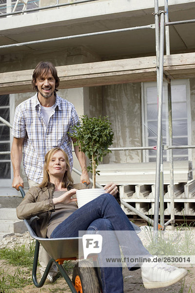 Young couple at construction site  woman sitting in wheelbarrow