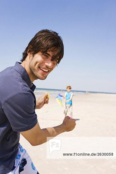 Deutschland  Ostsee  Vater mit Sohn (8-9) beim Drachenfliegen am Strand