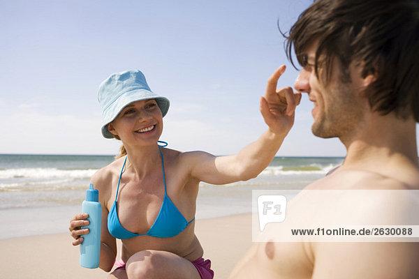 Deutschland  Ostsee  Junges Paar am Strand  Frau trägt Sonnencreme auf die Nase des Mannes auf