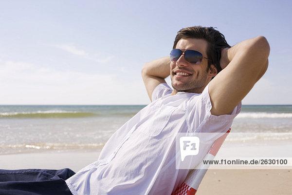 Deutschland  Ostsee  Junger Mann am Strand  lächelnd  Portrait  Nahaufnahme