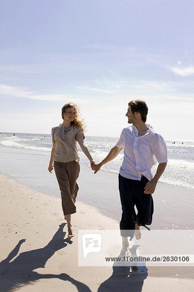 Deutschland  Ostsee  Junges Paar  das über den Strand läuft  Händchen haltend