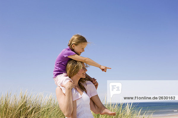 Deutschland  Ostsee  Mutter mit Tochter (6-7) auf den Schultern  Portrait
