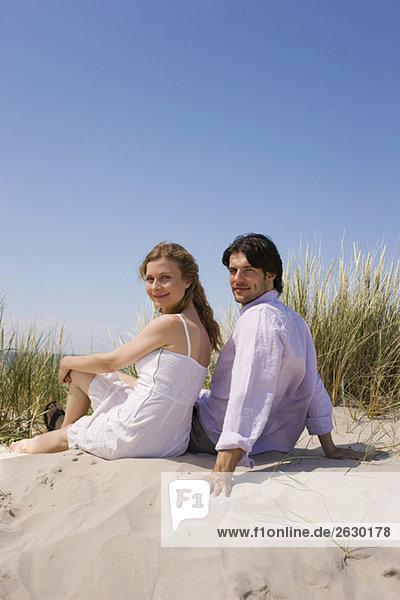 Deutschland  Ostsee  Junges Paar in grasbewachsener Sanddüne  Portrait