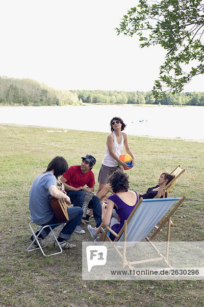 Germany  Leipzig  Ammelshainer See  Friends near lake making music