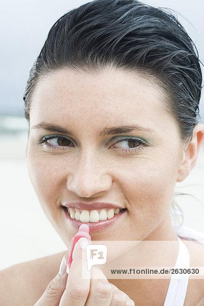 Frau setzen Lippenbalsam am Strand
