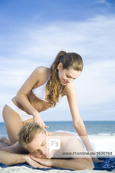 Frau setzen Sonnenöl am Strand