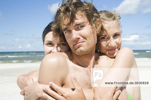 zwei Mädchen knuddeln Boy am Strand