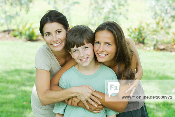Mother with son and teen daughter  smiling at camera  portrait