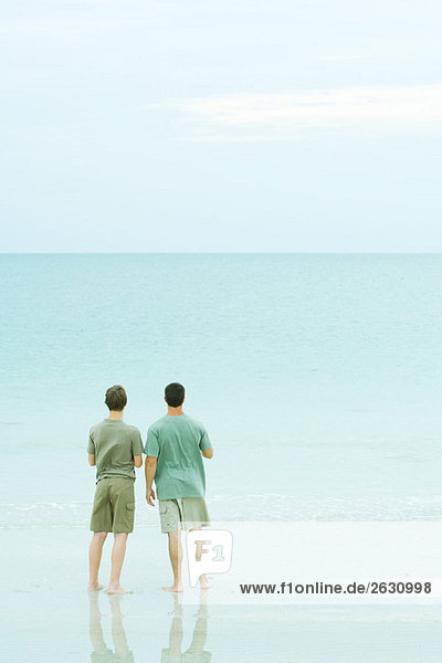 Father and son standing together on beach  looking at horizon
