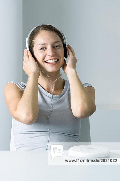 Frau hört tragbaren CD-Player  lächelt in die Kamera