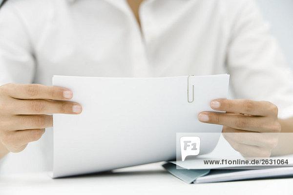 Frau hält Dokument mit Büroklammer gebunden,  abgeschnittene Ansicht