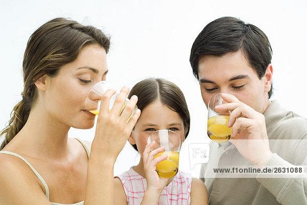 Familie trinkt gemeinsam Orangensaft