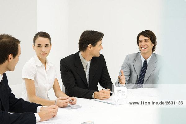 Geschäftspartner sitzen am Konferenztisch  schauen einander an  lächeln