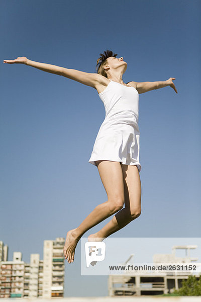 Woman jumping in midair  arms out  head back