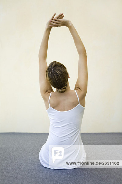 Woman sitting on the floor  stretching arms  rear view