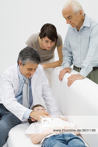 Arzt hört auf das Herz des jungen Patienten  Familie schaut zu