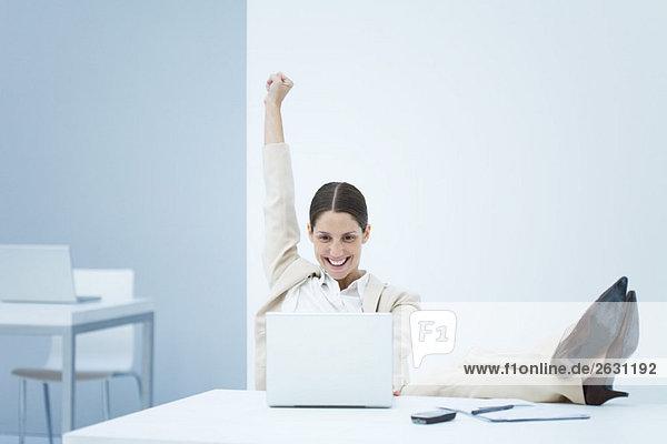 Junge Geschäftsfrau sitzt am Schreibtisch  lächelt den Laptop an und hebt einen Arm in die Luft.