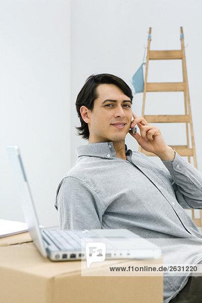 Mann mit Handy  lächelnd in die Kamera  Laptop auf Karton im Vordergrund sitzend