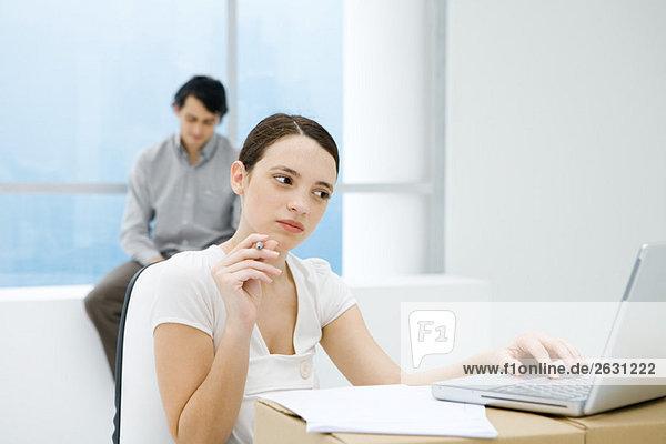 Junge Frau  die am Schreibtisch sitzt und einen Laptop benutzt