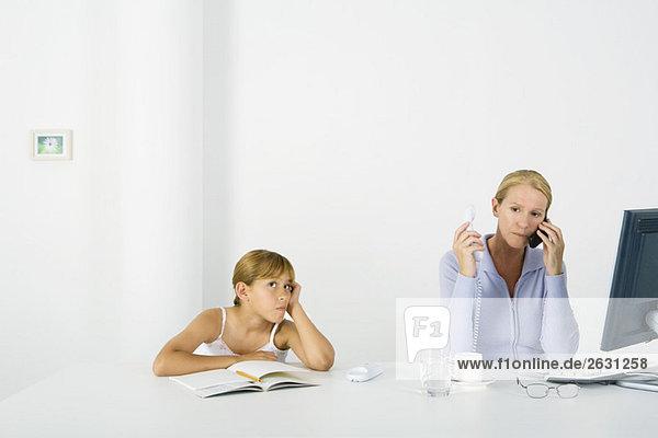 Frau sitzt vor dem Computer  benutzt Handy und Festnetztelefon  Tochter schmollt in der Nähe.