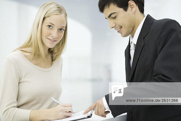Geschäftsmann hält Zwischenablage  Frau schreibt auf Dokument und lächelt in die Kamera