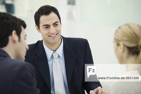 Professioneller Mann von Angesicht zu Angesicht mit einem Paar  lächelnd