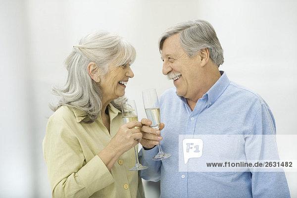 Seniorenpaar mit Champagnerflöten  die sich gegenseitig anlächeln