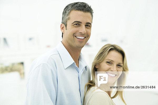 Paar lächelt in die Kamera  Frau lehnt sich an den Mann  Porträt