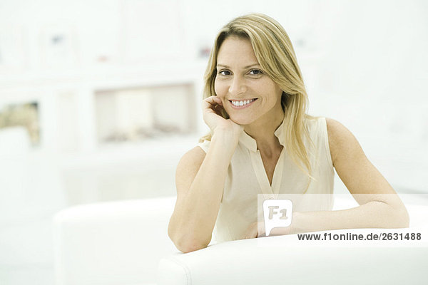 Frau stützt sich auf den Ellenbogen  lächelt in die Kamera  Porträt