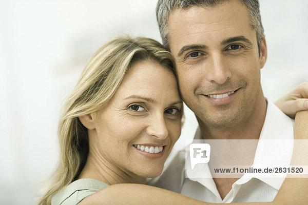 Paar lächelt in die Kamera  Frau wickelt Arme um den Mann  Porträt
