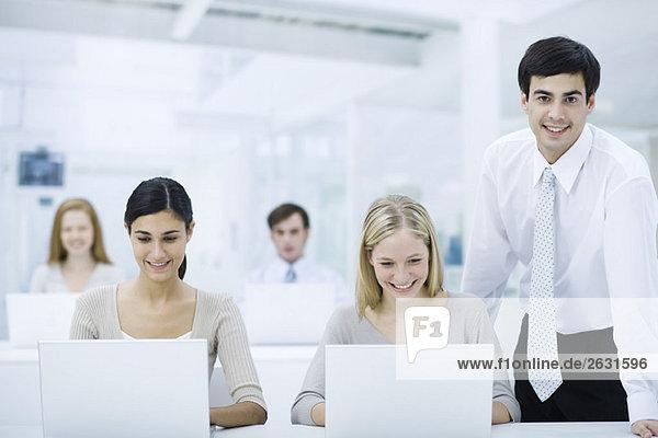 Vorgesetzter steht neben Mitarbeitern  die an Laptops arbeiten und lächelt in die Kamera.