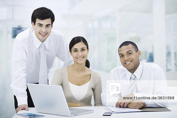 Profis versammelt um Laptop-Computer  lächelnd auf die Kamera