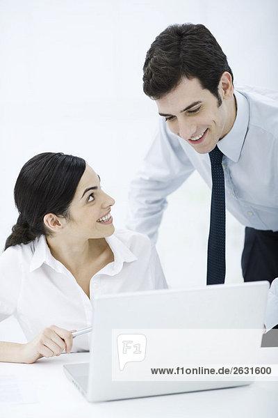 Professionelle Frau sitzend mit Laptop  männlicher Kollege schaut ihr über die Schulter  beide lächelnd